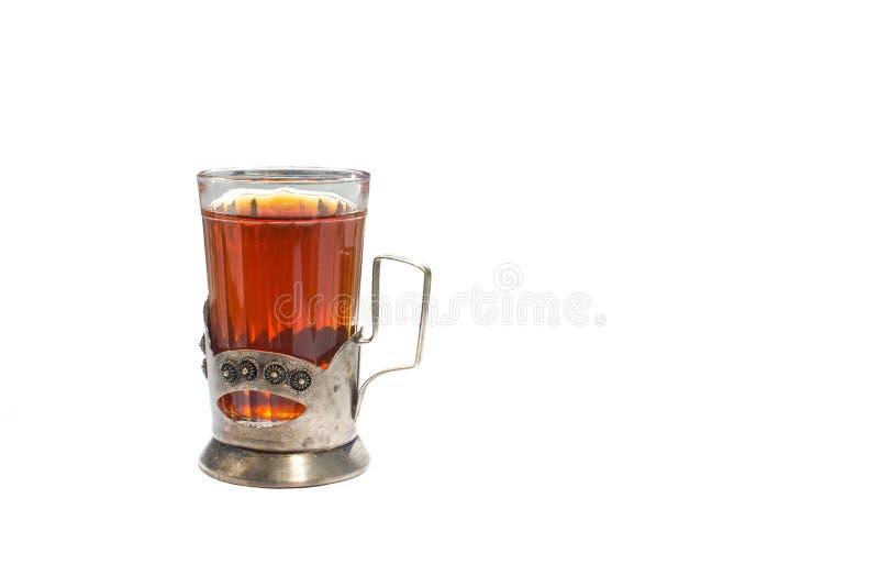 Starkt varmt svart te i en exponeringsglaskopp i en metallkopph?llare p? en vit bakgrund royaltyfria foton