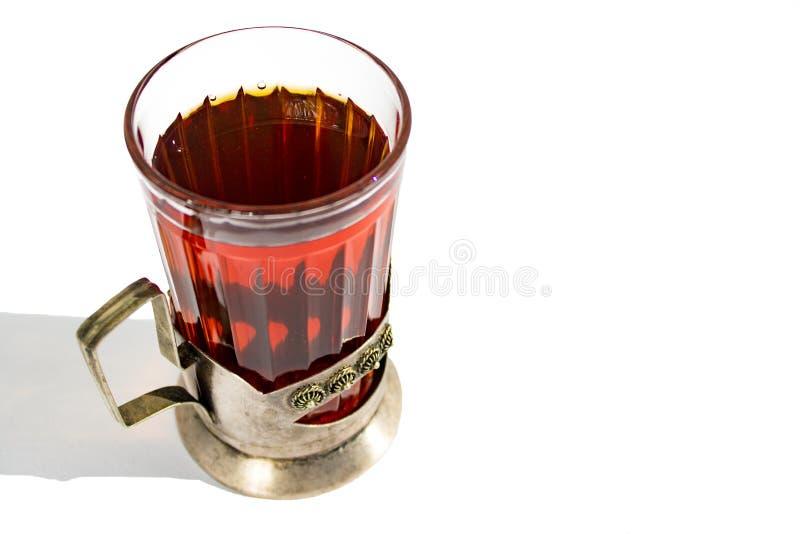 Starkt varmt svart te i en exponeringsglaskopp i en metallkopph?llare p? en vit bakgrund med en skugga arkivbilder