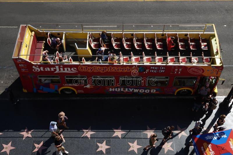Starline游览在游人旁边停放的双层甲板船观光巴士走在好莱坞星光大道 免版税图库摄影
