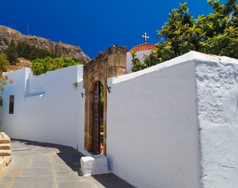 Starożytny Grek architektura z tradycyjnymi drzwiami i dekoracyjnym brukiem w Lindos miasteczku, Rhodes wyspa, Grecja fotografia royalty free