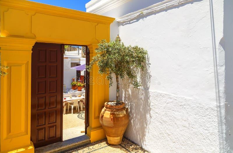 Starożytny Grek architektura z tradycyjnymi drzwiami i dekoracyjnym brukiem w Lindos miasteczku, Rhodes wyspa, Grecja, Europa zdjęcia stock