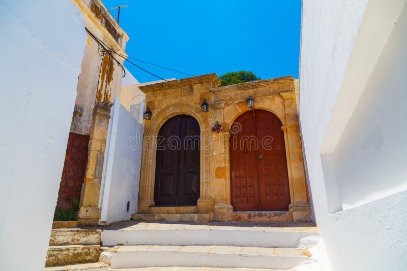 Starożytny Grek architektura z tradycyjnymi drzwiami i dekoracyjnym brukiem w Lindos miasteczku, Rhodes wyspa, Grecja fotografia stock