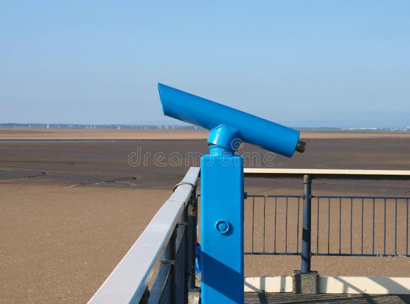 Staromodny błękitny teleskop na końcówce southport molo w Merseyside z nasłonecznionym lata niebieskim niebem i plażą zdjęcia stock