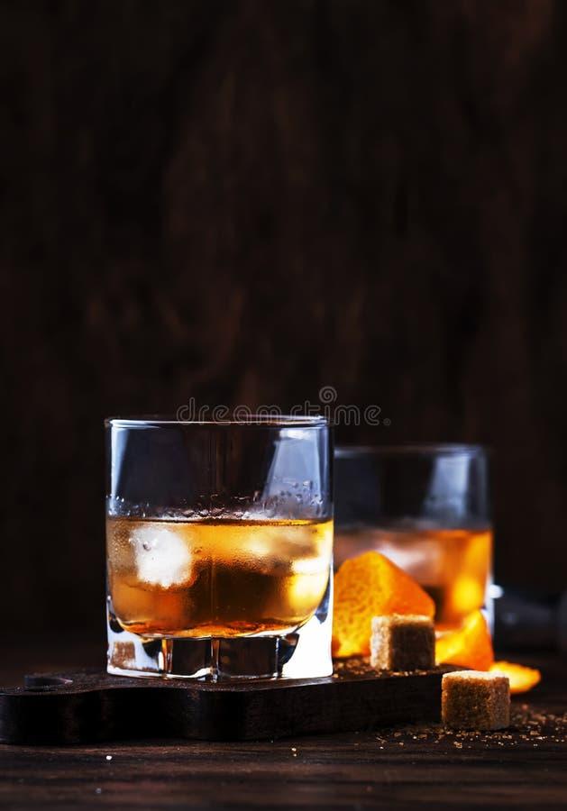 Staromodny - klasyczny alkoholiczny koktajl z bourbonu whisky, cukierem i lodem w retro szkłach na rocznika barze, gorzkiego, trz zdjęcia stock