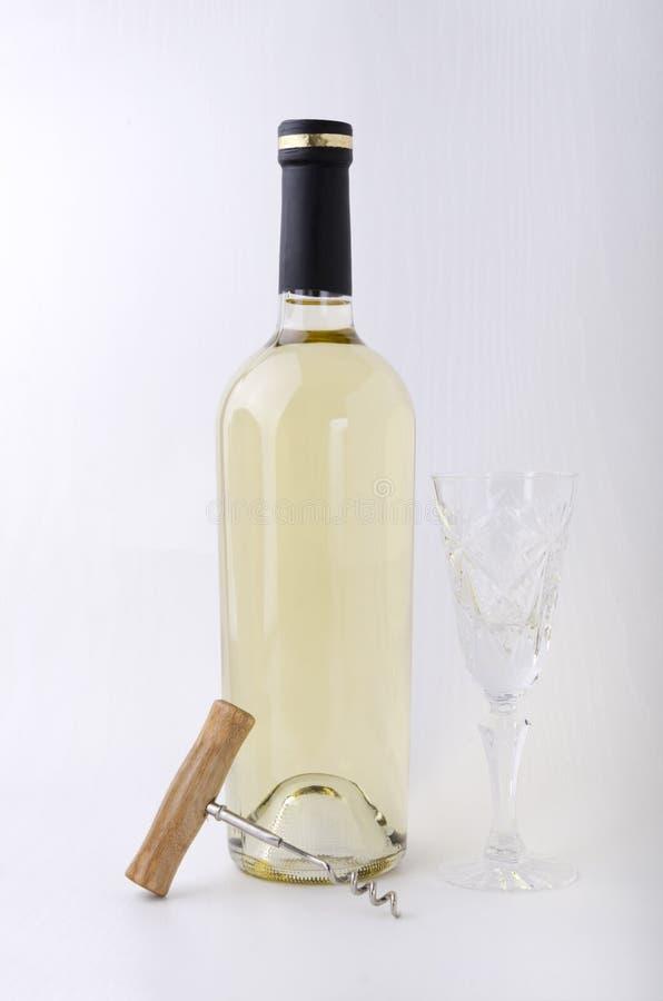 Staromodny wina szkło, pieczętująca butelka wino i corkscrew na białej powierzchni przeciw biel ścianie, obrazy royalty free