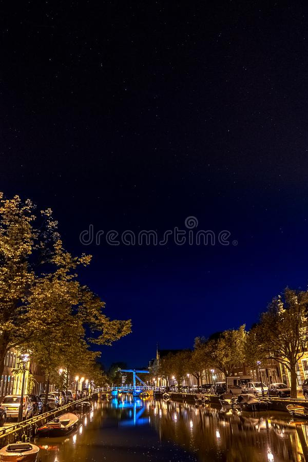 Starry night along a Dutch city canal with urban style, boates, stock images