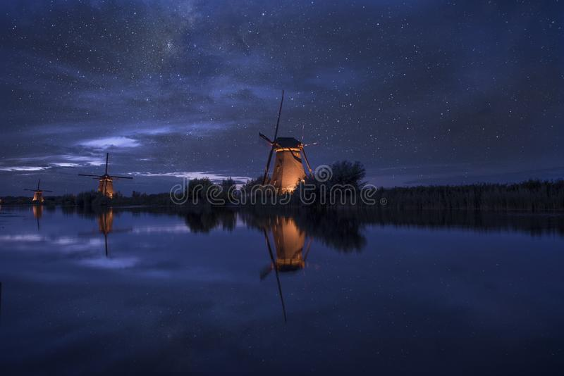 Starry night with dutch windmills in Kinderdijk stock image