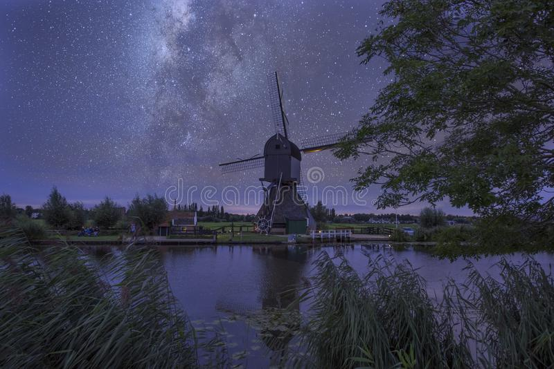 Starry night with dutch windmills. Starry night with milkyway with dutch windmills in Kinderdijk in the netherlands stock photos