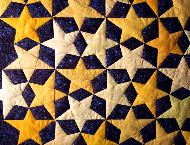 Starry night handcrafted cotton fabric quilt. Quilted gold and white stars on blue background exhibited in Arkansas Historic Museum stock image