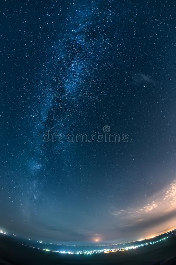 Night sky and milky way over a bright city royalty free stock photos