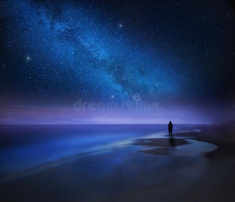 Starry night sky over sea and beach with man silhouette stock image