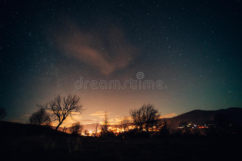 Starry night sky over town royalty free stock image