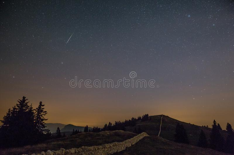 Starry Night Sky and Shooting Stars over Mountains stock image
