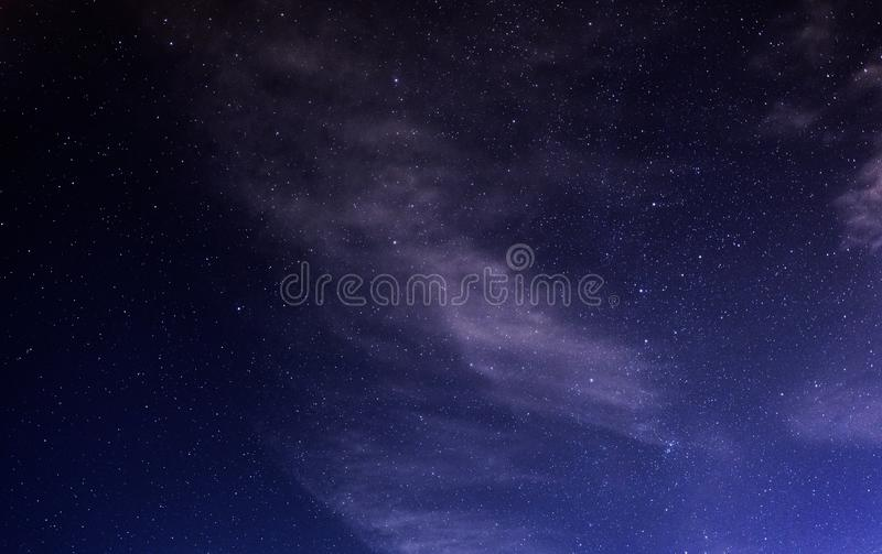Starry night sky with soft clouds. Stars in the night blue sky with soft white clouds stock photo