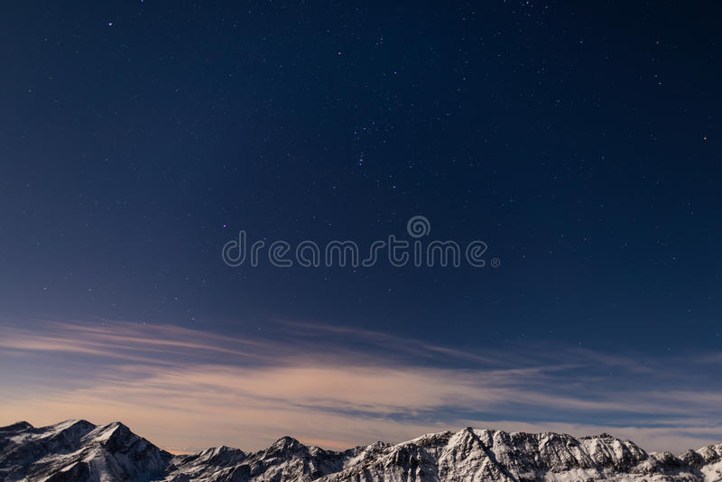 The starry sky above the Alps in winter, Orion Constellation. The starry sky captured on the Alps in winter. The Pleiades, Orion Constellation, Betelgeuse and stock images