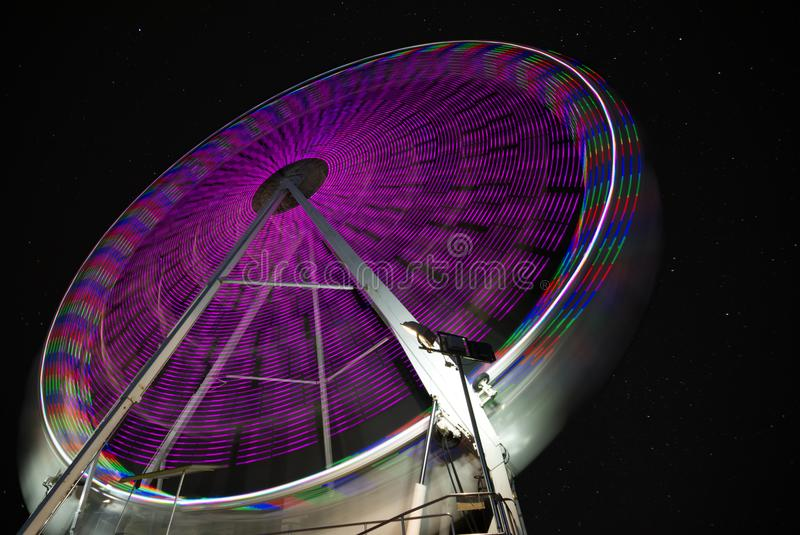 Starry sky behind ferris wheel. Long exposure royalty free stock image
