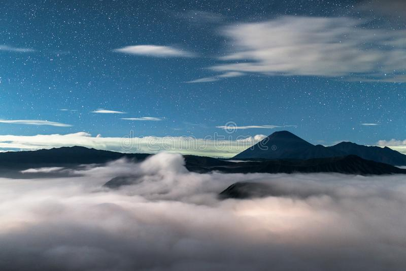 starry sky in the landscape with volcanoes in the clouds, Volcano Bromo National Park royalty free stock photography