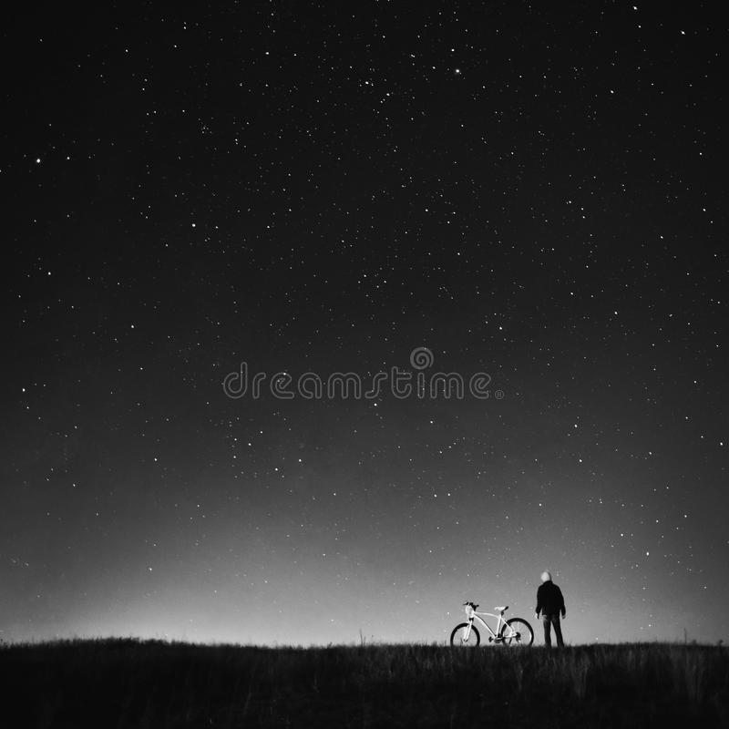 Black and white art monochrome photography. Starry sky, night photography, astrophotography, the silhouette of a man, a man standing next to a mountain bike on royalty free stock image