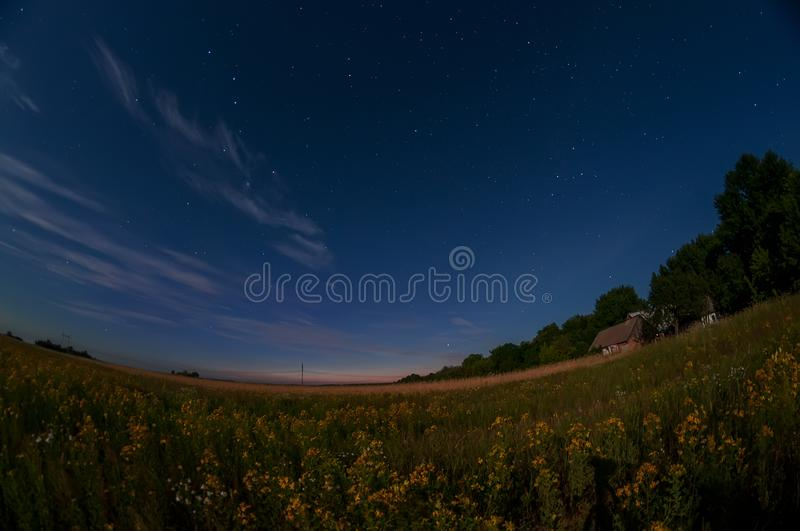 Starry sky over the expanses of fields and a small rural house.night photo. A curved horizon line as an artistic idea, a small ho. Use and a round globe stock photo