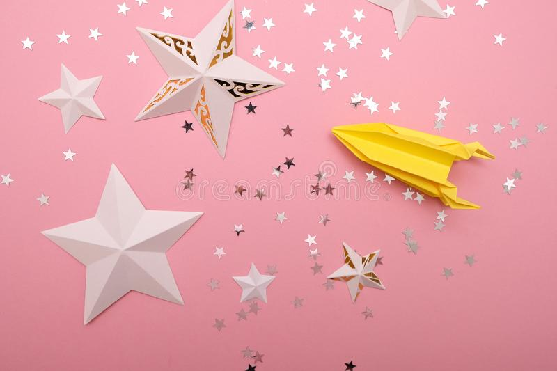 Stars cut from paper with sequins in the star shape. On pink background. Space concept royalty free stock images