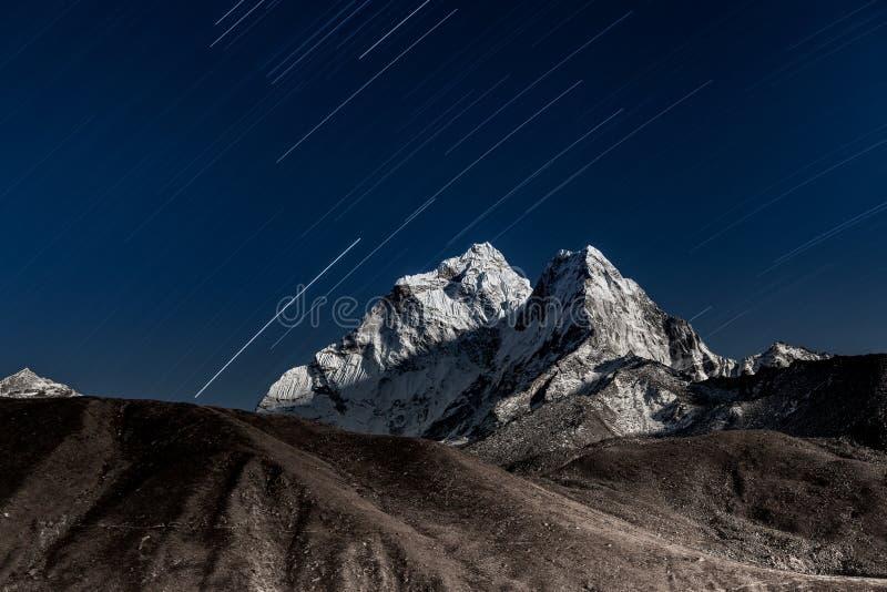 Stars falling above Ama Dablam mountain peak lit. stock photography