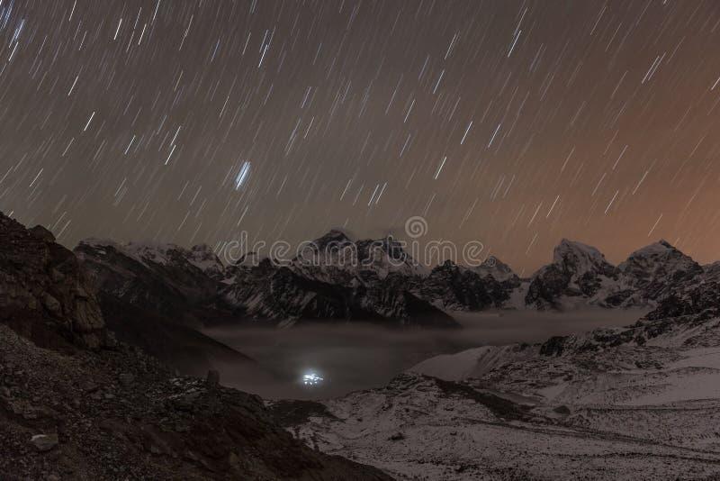 Stars falling above Himalayan mountain range lit. stock photo