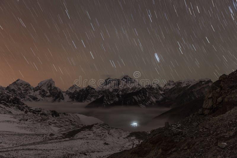 Stars falling above Himalayan mountain range lit. stock image