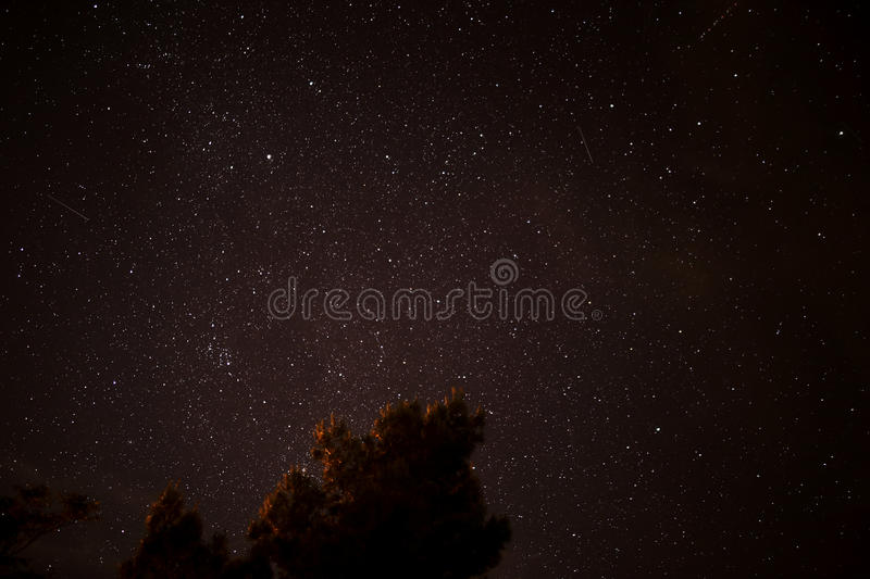 Stars Filling Up the Night Sky. Long exposure revealing countless stars and the paths of two satellites (two solid streaks) and an airliner (dotted streak near royalty free stock image