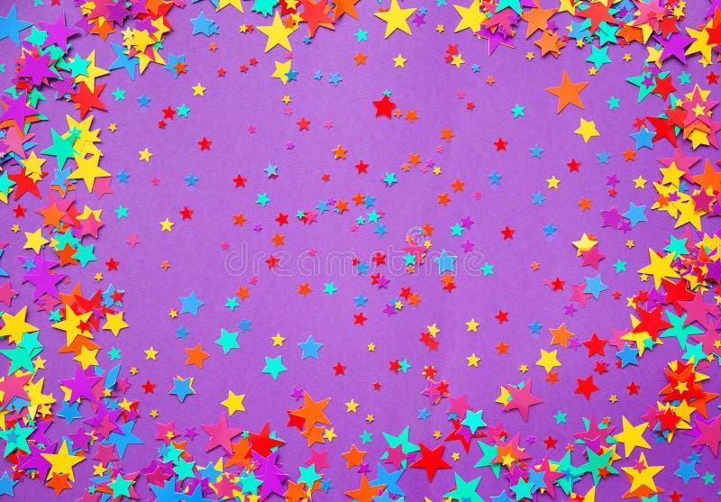 Stars i coriandoli su un fondo porpora fotografia stock libera da diritti