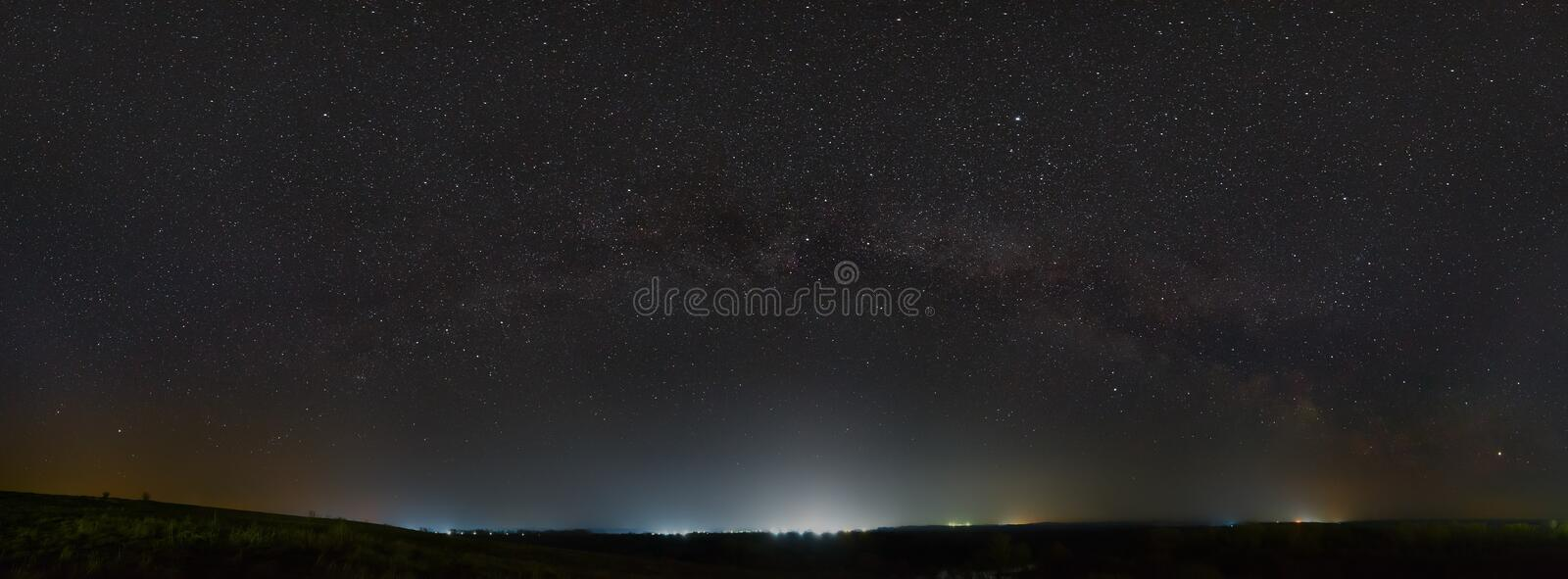 Stars of the Milky Way in the night sky. Light pollution from street lamps above the horizon royalty free stock images