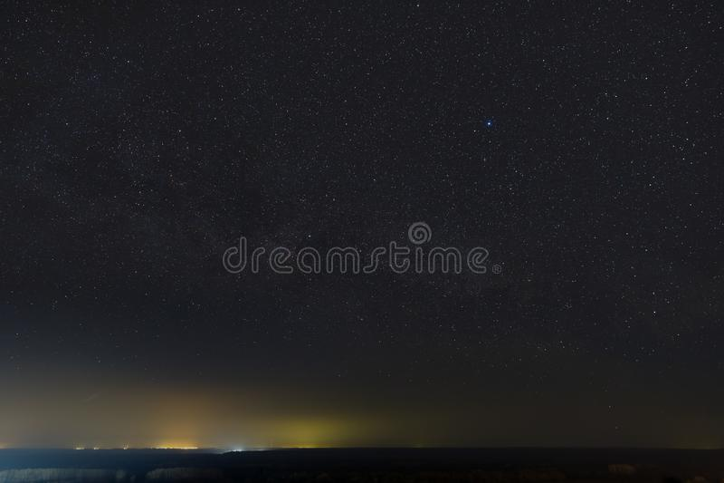 Stars of the Milky Way in the night sky. Light pollution from street lamps above the horizon.  royalty free stock photos