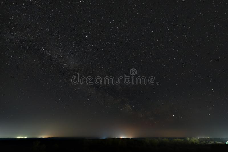 Stars of the Milky Way in the night sky. Light pollution from street lamps above the horizon.  royalty free stock photography