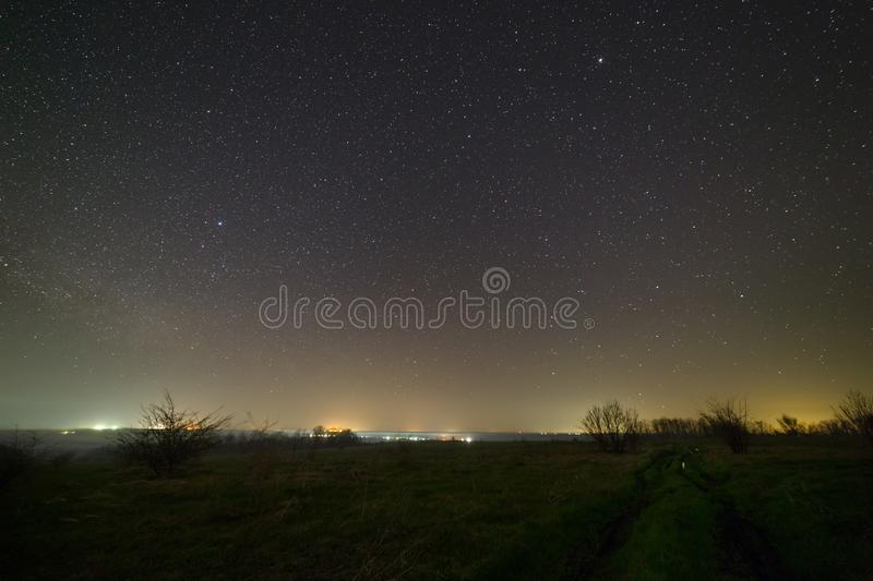 Stars in the night sky over a dirt road. Landscape photographed with a long exposure.  royalty free stock images
