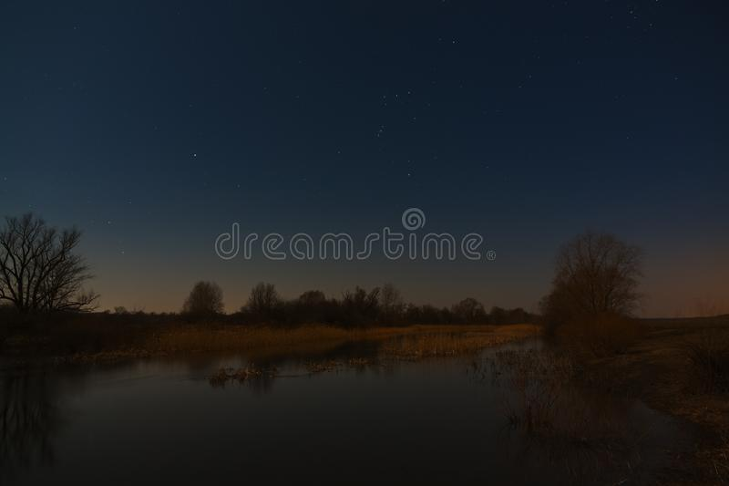 Stars in the night sky over the river. Early spring in central Russia.  stock photography