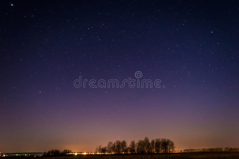 Stars. In the night sky, with some lights on horizon line royalty free stock image