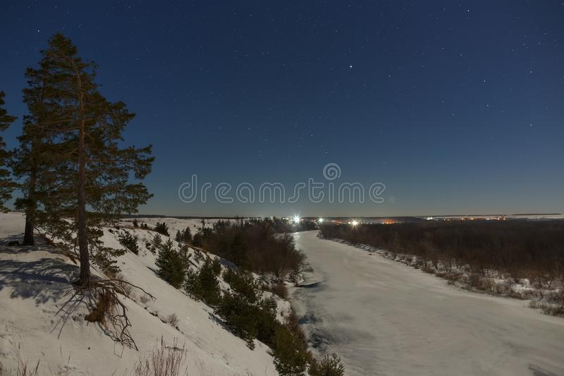 Stars in the night sky. Winter landscape with a frozen river photographed under the full moon.  royalty free stock photography