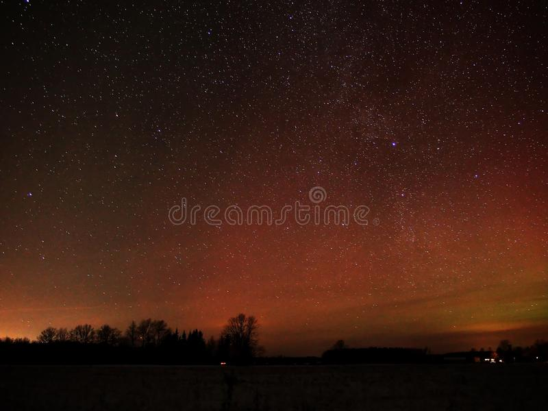 Night sky stars and red polar lights royalty free stock photo