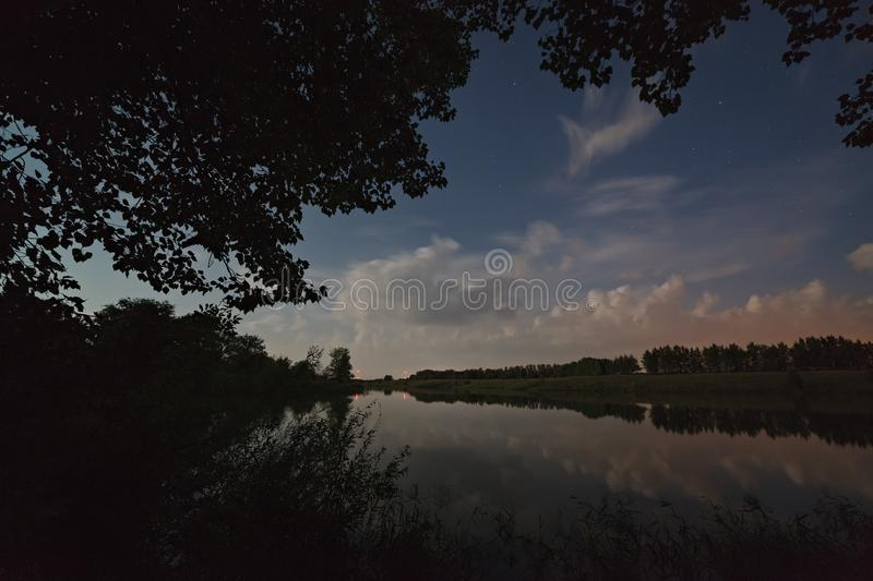 Stars in the sky with clouds. Night landscape with a lake royalty free stock images