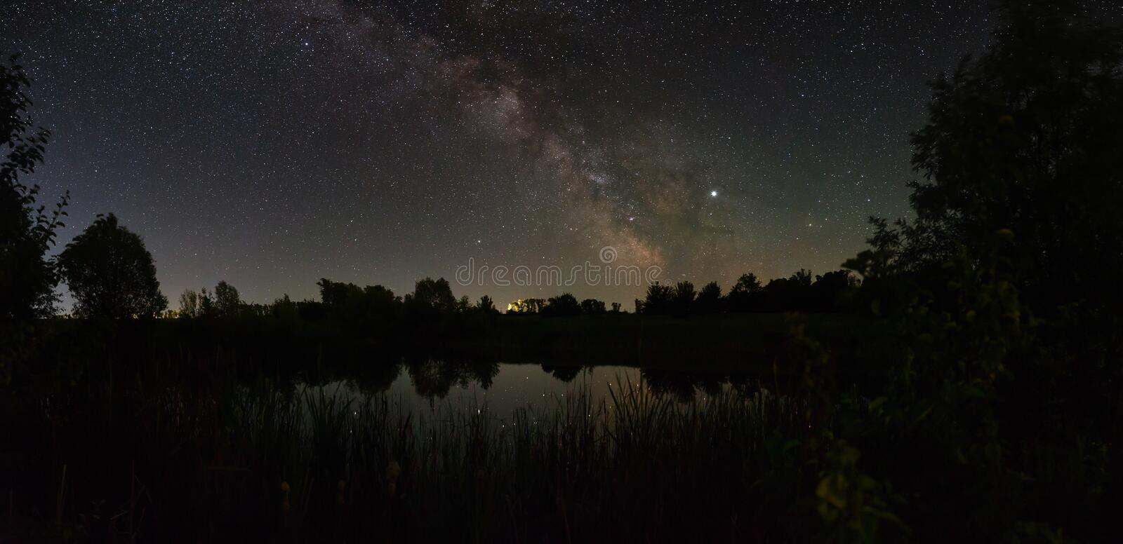 Stars in the sky at night. Panoramic view of the bright Milky Way over the lake. Photographed with a long exposure.  stock photos