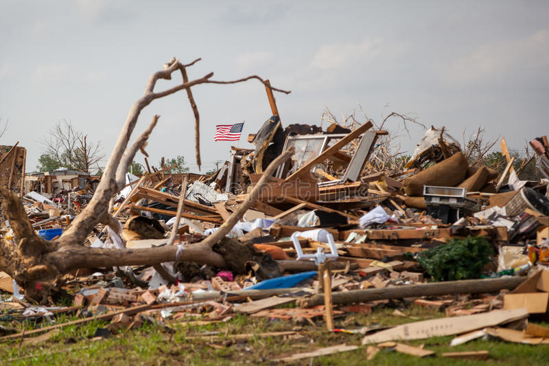 Tornado Damage American Flag. The American flag flying amid debris in Moore, Oklahoma after a deadly tornado destroyed much of the down stock photo