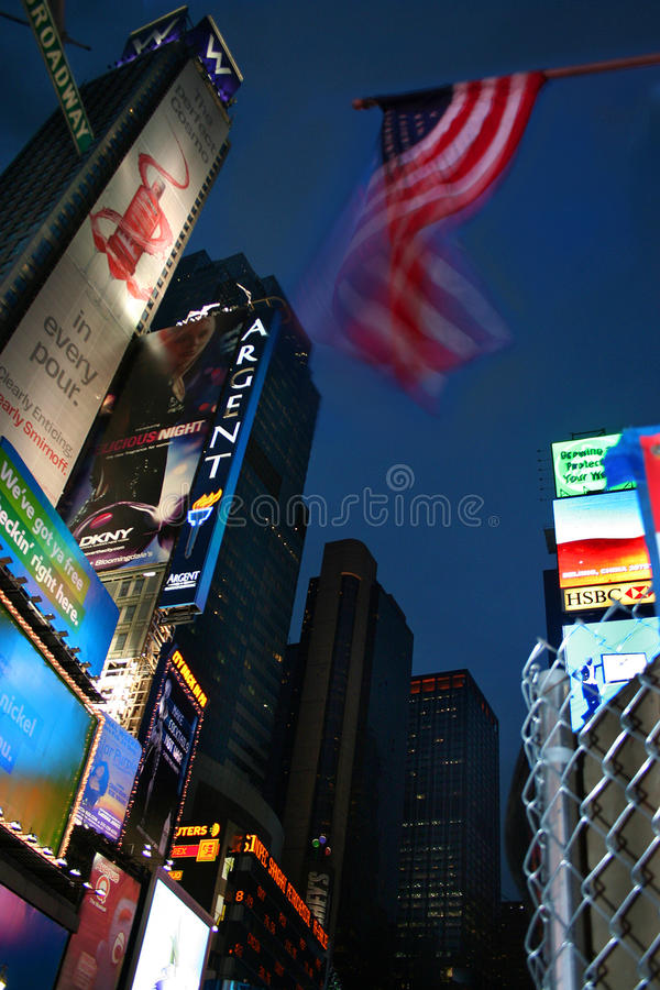 Stars and stripes in Times Square. Night time shot looking up in Times Square underneath the American flag stock photos