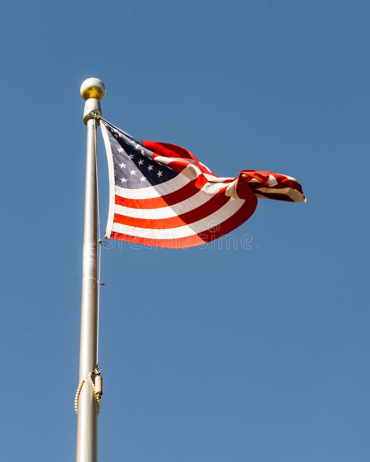 Stars and Stripes Twisting in the Wind. An American flag twisting in the wind on a silver flag pole with a clear blue sky in the background royalty free stock images