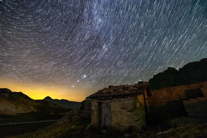 Stars trails and isolated house in switzerland alps stock photos