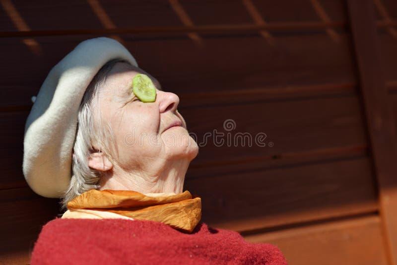 Starsi kobiety kładzenia ogórki na twój oczach obrazy stock