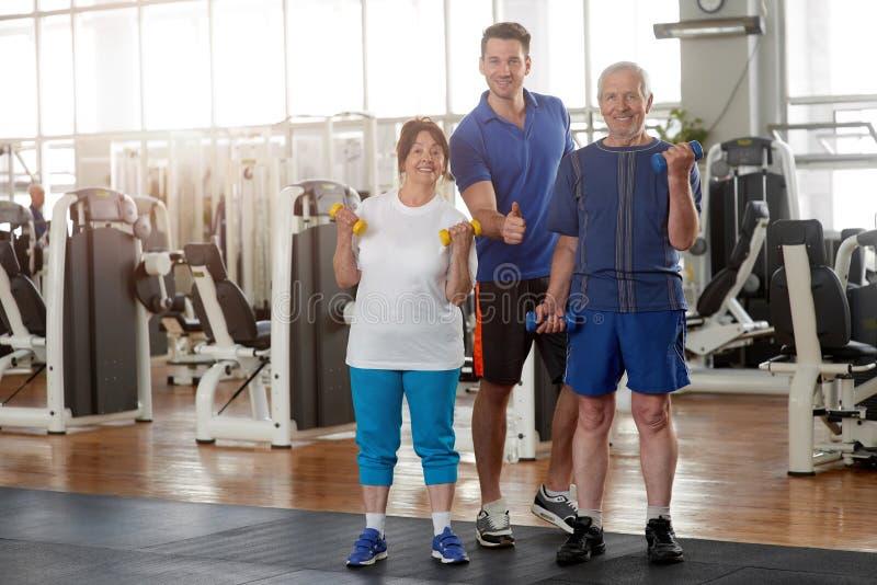 Starsi ludzi z osobistym trenerem przy gym zdjęcia royalty free