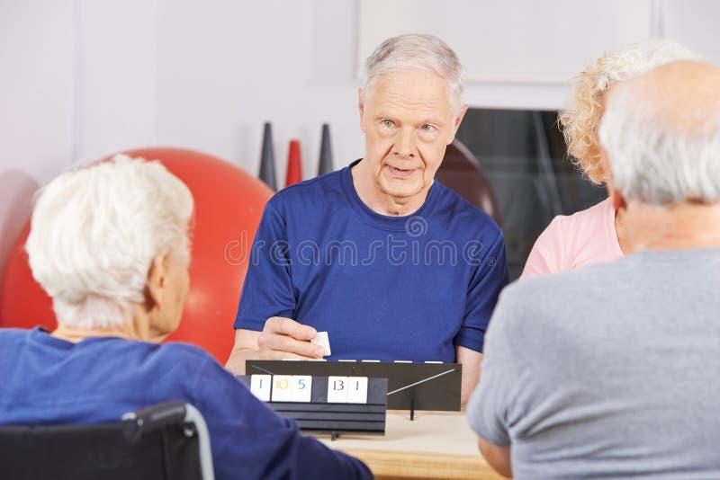 Starsi ludzie bawić się rummikub w karmiącym domu fotografia stock