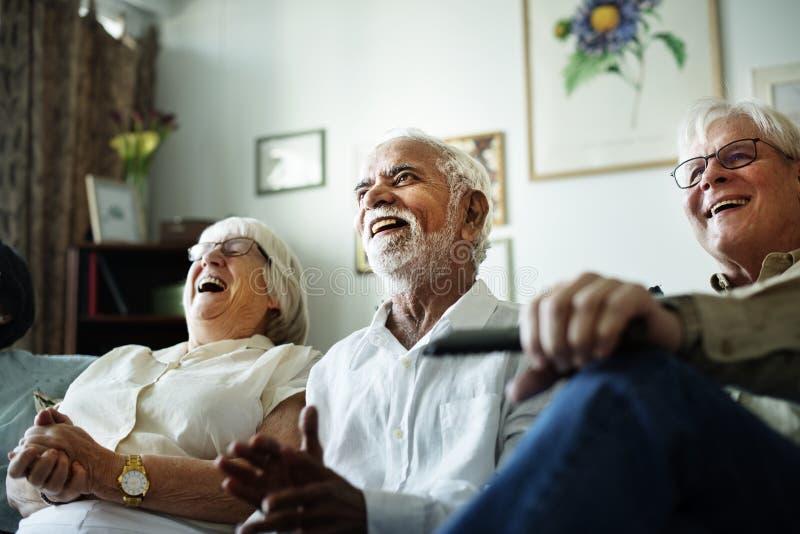Starsi ludzie ogląda programa komediowego wpólnie zdjęcia stock