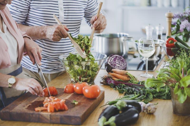 Starsi ludzie przygotowywa zdrowego gościa restauracji fotografia stock