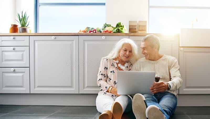 Starsi ludzie używa laptop w kuchni zdjęcia royalty free