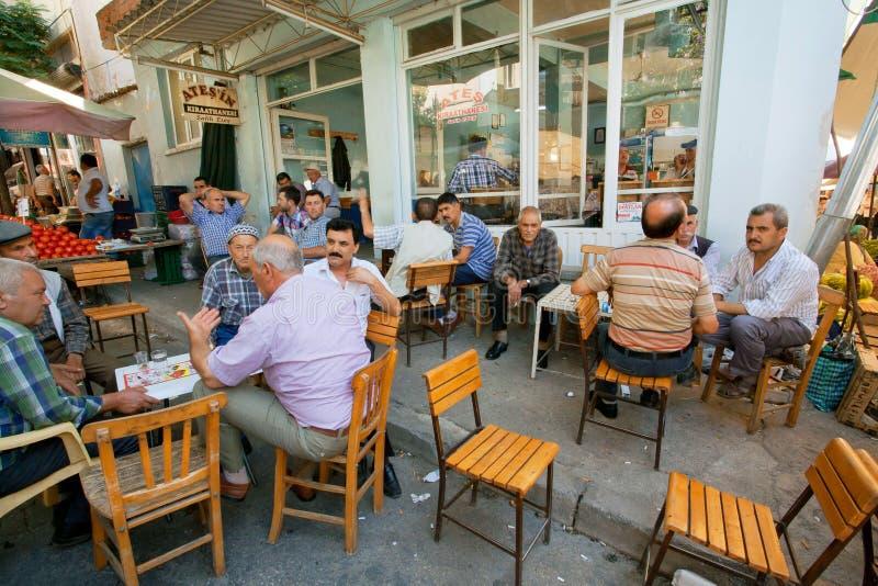 Starsi mężczyzna siedzi wokoło stołów i opowiada w nieociosanej kawiarni wioska obraz stock